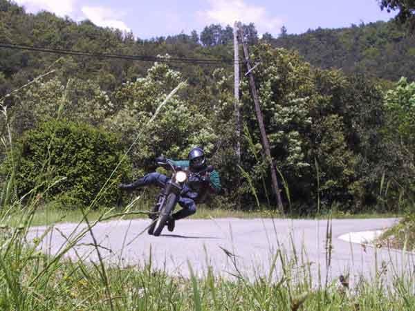 Motorrijder met arm en been uitgestoken